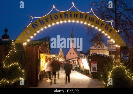 Sign over gate and stalls, Christmas Market (Christkindlmarkt) on Kapellplatz Square, at twilight, Altotting, Bavaria, - Stock Photo