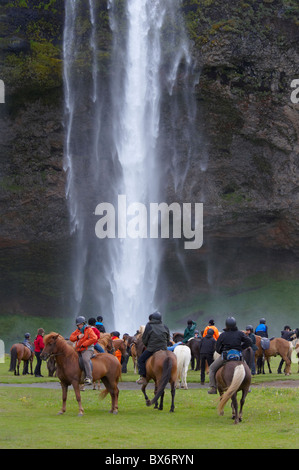 Horse riders taking a rest at Seljalandsfoss on the south coast of Iceland - Stock Photo