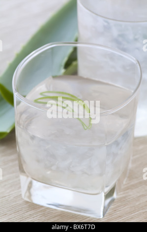 Glass with aloe drink and leaf as closeup - Stock Photo