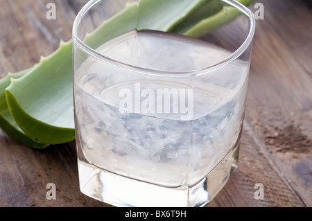 Glass with aloe drink and leaf as closeup on old wood - Stock Photo