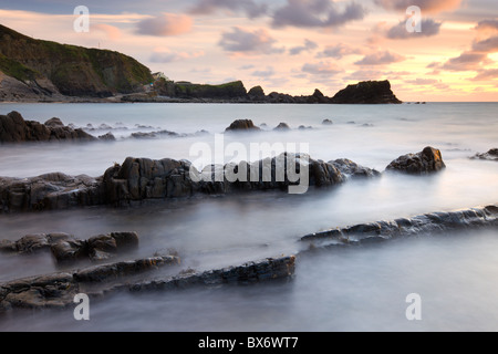 Beautiful sunset over Hartland Quay, from the rocky shores of Hartland Beach, North Devon, England. Autumn (September) - Stock Photo