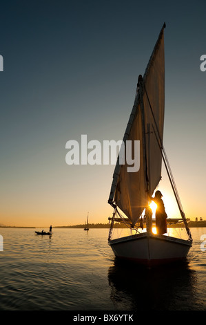 A stunning and beautiful image of a traditional Egyptian sail boat called a felucca on the Nile at sunset with girl - Stock Photo