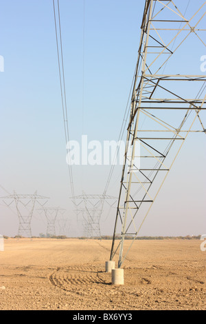 Close up of a transmission tower and power lines in a plowed field. Kern County, California. U.S.A. - Stock Photo
