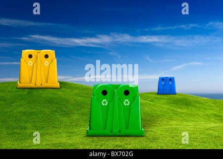 Recycle containers for glass, metal, plastic and paper waste placed on a green meadow landscape - Stock Photo