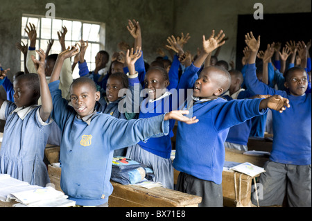 Schoolchildren in classroom, offering traditional Kikuyu welcome, Karunga Primary School, Kenya - Stock Photo