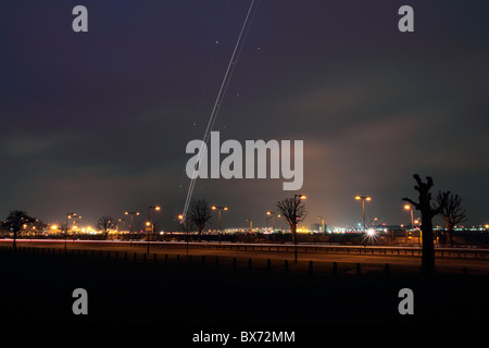 Light trail from an aircraft taking off from London Heathrow airport England - Stock Photo