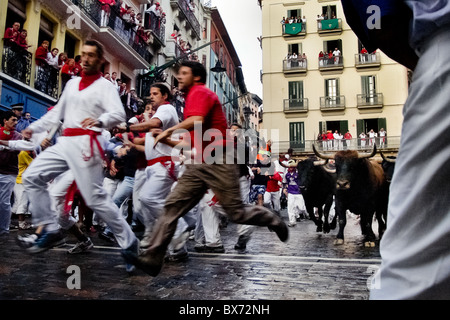 The Running of the Bulls (encierro de los toros) during the San Fermín festival in Pamplona, Spain. - Stock Photo