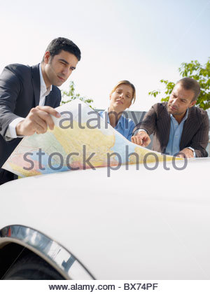 Businesspeople looking at map - Stock Photo