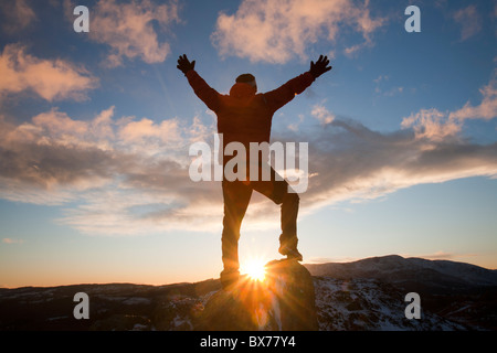 A mountaineer on Todd Crag summit in the Lake District, UK, at dusk. - Stock Photo