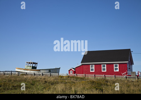 Maritime house painted red with boat on lawn, Iles de la Madeleine (Magdalen Islands), Gulf of St. Lawrence, Quebec, - Stock Photo