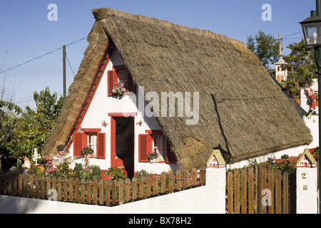 A Madeiran man sits outside a traditional Palheiro A-frame house in the town of Santana, Madeira, Portugal, Europe - Stock Photo