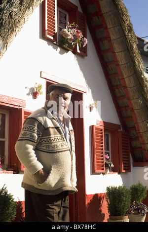 A Madeiran man stands outside of a traditional Palheiro A-frame house in the town of Santana, Madeira, Portugal, - Stock Photo