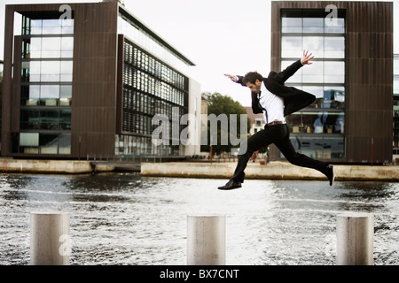 Man jumping from pole to pole - Stock Photo