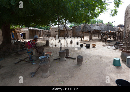 Yard of a village where a woman is busy in the process of making butter out of shea (karité) nuts. Mali, West Africa. - Stock Photo