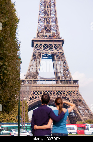Couple look at Eiffel Tower in Paris - Stock Photo