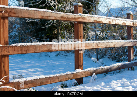 A snow covered frosty wooden fence guarding a winter wonderland. - Stock Photo