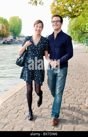 couple arm in arm by the Seine Paris - Stock Photo