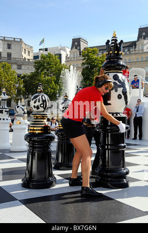 Woman moving giant ceramic chess piece during public tournament part of the London Design Festival - Stock Photo