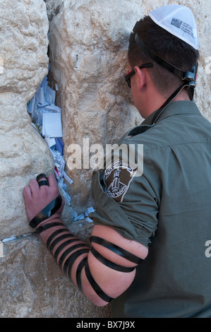 israeli border guard praying at the western wall with phylacteries. Jerusalem. israel - Stock Photo