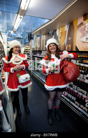 LONDON, ENGLAND - Santacon London 2010, two female Santas shopping at Marks & Spencer store - Stock Photo