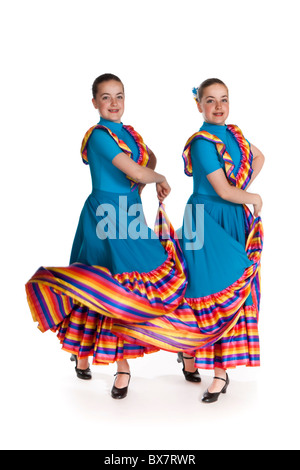 Studio shot of beautiful young identical twins in colourful Mexican national dancing costume, against white background - Stock Photo
