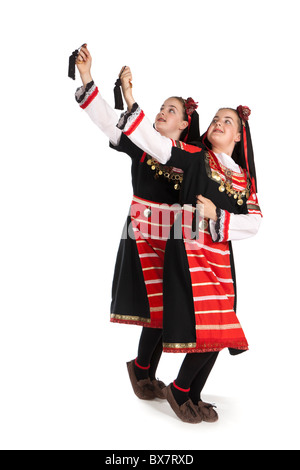 Studio shot of beautiful young identical twins in colourful Romanian national dancing costume - Stock Photo