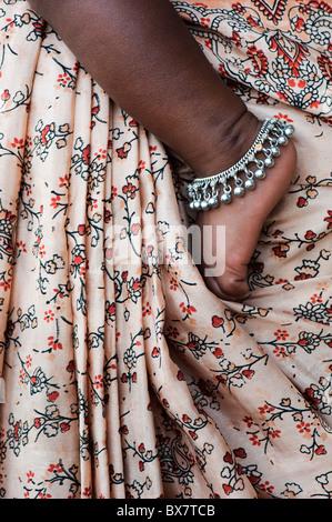 Indian babies foot against mothers patterned sari. Andhra Pradesh, India - Stock Photo