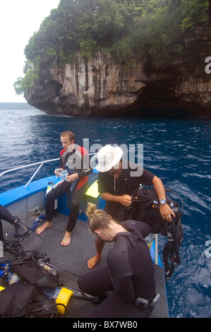 Scuba divers preparing to dive Boat Cave (visible in cliff in background), Christmas Island, Indian Ocean. No MR - Stock Photo
