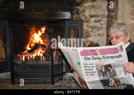 Senior woman pensioner retiree reading a Daily Telegraph broadsheet newspaper reporting pension cuts by an open - Stock Photo