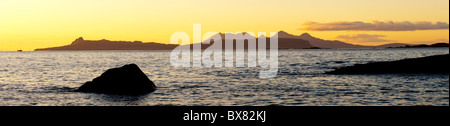 Beautiful shimmering seascape looking toward the Scottish islands of Rhum and Eigg at sunset from the Ardnamurchan - Stock Photo