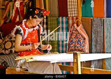 Young woman weaving in textile shop, Lijiang, Yunnan, China - Stock Photo