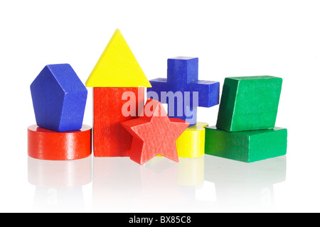Colorful geometrical blocks arranged on white background with reflection - Stock Photo