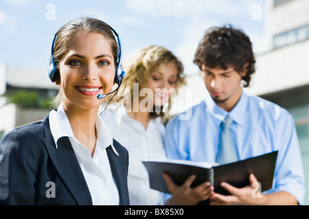 Portrait of smiling woman with headset on her head and two reading people on the background - Stock Photo