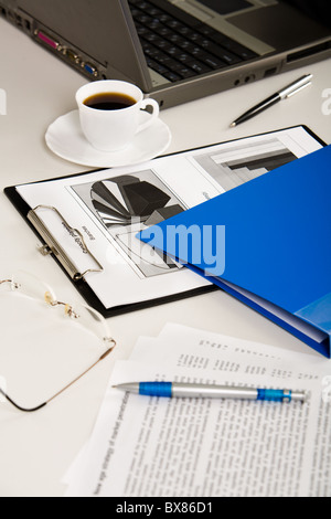 Business documents, laptop, eyeglasses, pens, folder and cup of coffee are lying on white table - Stock Photo