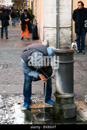 man drinking at a water fountain in Rome, Italy - Stock Photo