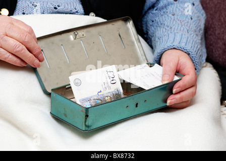 pensioner with cash tin and English currency - Stock Photo