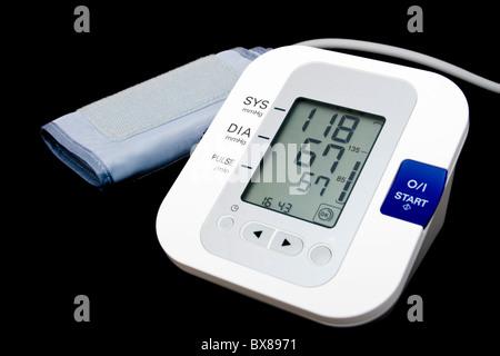 Digital blood pressure monitor isolated on black - Stock Photo