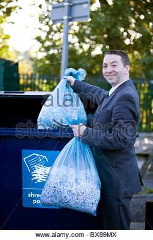 A businessman recycling bags of shredded paper - Stock Photo