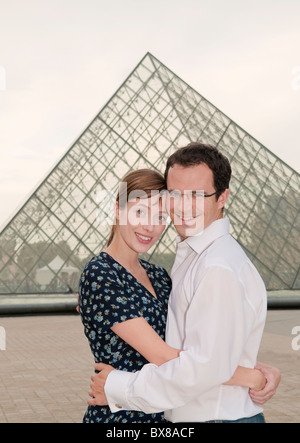 Happy couple embrace at the Louvre Paris - Stock Photo
