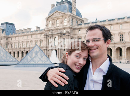 Happy couple embrace outside the Louvre - Stock Photo