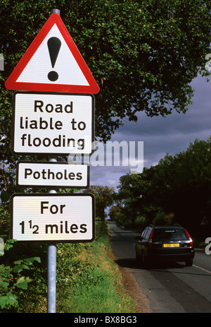 warning roadsign of road liable to flooding and potholes UK - Stock Photo
