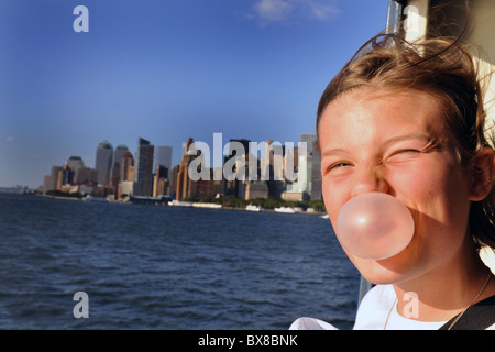 teenage girl looks out over the New York Manhattan skyline USA while blowing her bubblegum.  FULLY MODEL RELEASED/CONSENTED - Stock Photo