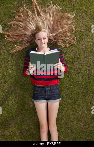 Girl lying reading a book - Stock Photo