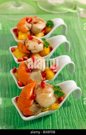 Scallops with mango and pomegranate. Recipe available. - Stock Photo