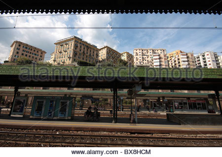 Buildings on a cliff tower over the central train station in Genova, Italy. - Stock Photo