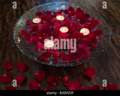 Red rose petals and candles floating in glass bowl - Stock Photo