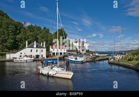 A yacht has entered the Crinan Canal basin at Crinan in Knapdale Argyll & Bute Scotland from Loch Crinan - Stock Photo