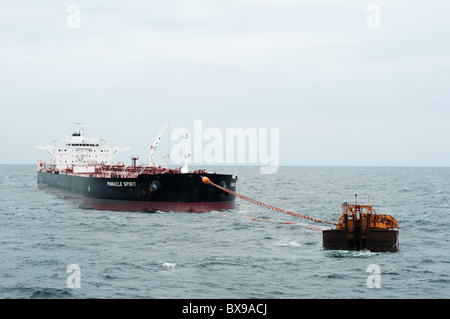 Oil tanker ship anchored in offshore area waiting to be loaded by a production oil rig from petrobras, brazilian oil company.