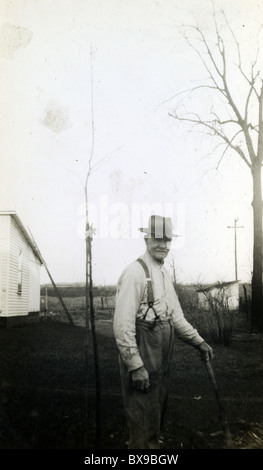 Old man with cane on farmstead farmer eldery male fashion suspenders - Stock Photo