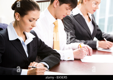 Portrait of business people studying a text at a seminar - Stock Photo